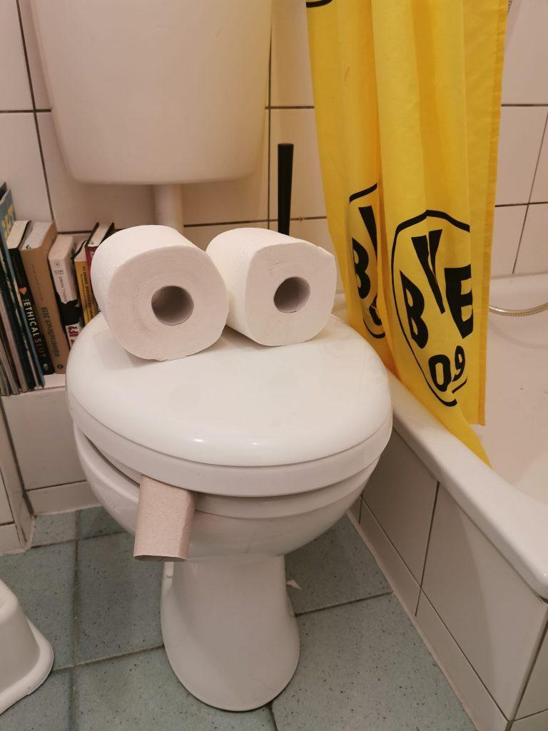 Grinsende und rauchende Toilette mit Klopapierrollen.